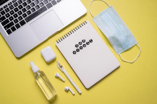 Вид сверху ноутбука рядом с медицинской маской с дезинфицирующим средством для рук Бесплатные Фотографии