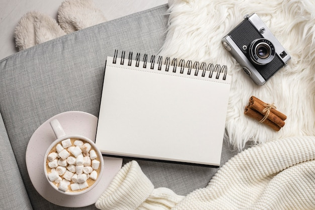 カメラとマシュマロとホットココアのカップとノートブックの上面図 無料写真