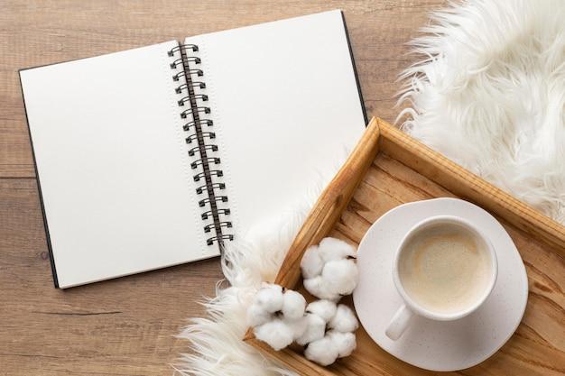 一杯のコーヒーと綿の花とノートブックの上面図 無料写真