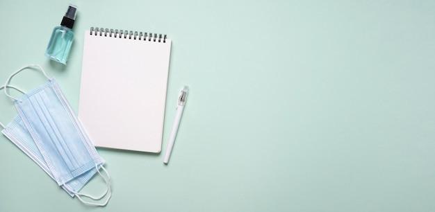 Вид сверху ноутбука с дезинфицирующим средством для рук и медицинскими масками Premium Фотографии