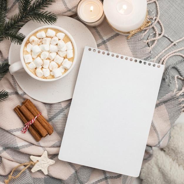 マシュマロとシナモンのマグカップとノートブックの上面図 無料写真