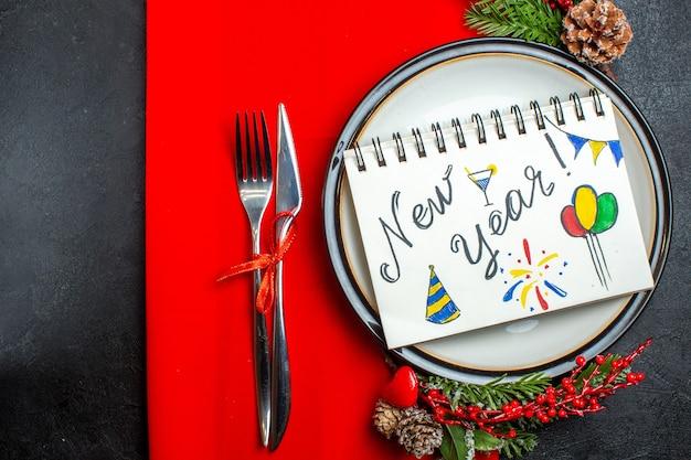 赤いナプキンにセットされた装飾アクセサリーモミの枝とカトラリーとディナープレートに新年の書き込みと図面とノートブックの上面図 無料写真