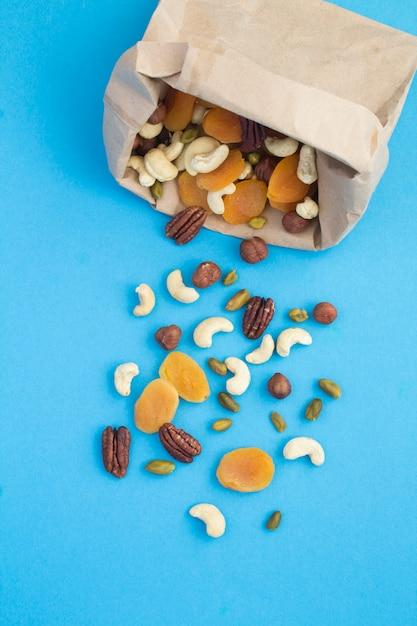 青い背景の上の紙袋にナッツとドライアプリコットの上面図 Premium写真