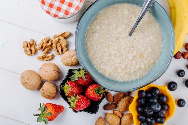 Вид сверху овсяной каши в миску и свежие ягоды и орехи на деревянный белый деревенский стол Бесплатные Фотографии