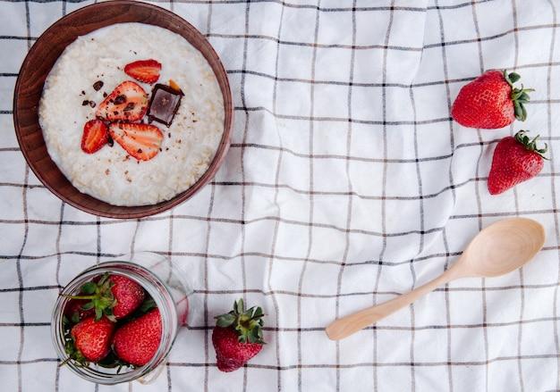 コピースペースの格子縞の生地に新鮮な熟したイチゴと木のスプーンをボウルにオートミールのお粥の平面図 無料写真