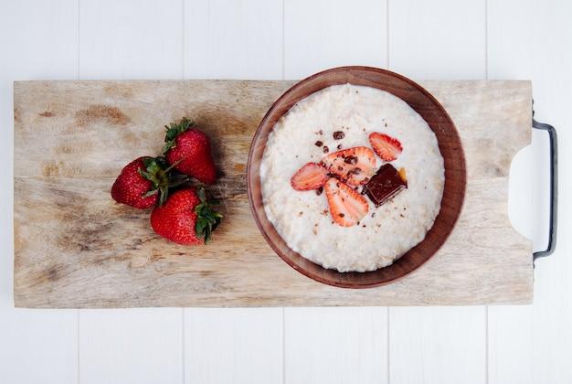 素朴な木製のまな板に新鮮な熟したイチゴと木製のボウルにオートミールのお粥の平面図 無料写真