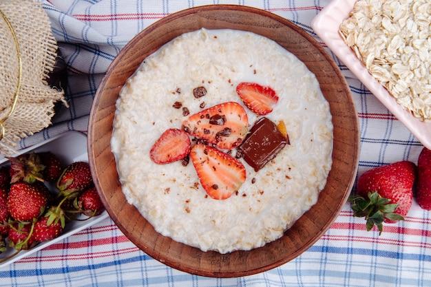 新鮮なイチゴとチョコレートのオートミールのお粥の平面図生地に木製のボウルに 無料写真