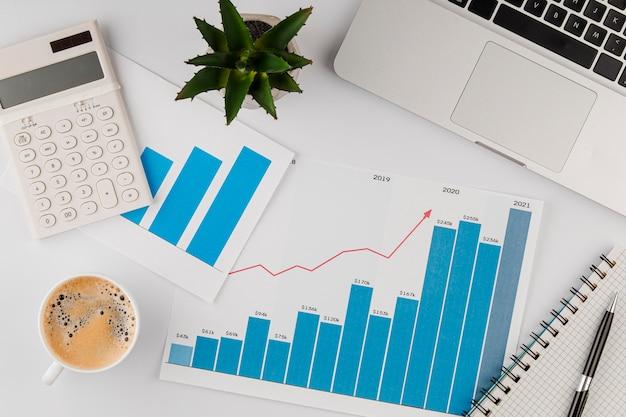 Вид сверху офисного стола с диаграммой роста и чашкой кофе Бесплатные Фотографии
