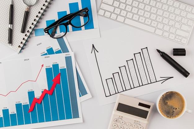 Вид сверху офисного стола с диаграммой роста и очками Бесплатные Фотографии