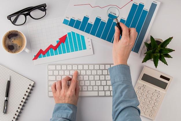 成長チャートとキーボードの手とオフィスデスクの上面図 無料写真