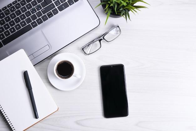オフィスの作業スペース、ノートパソコンのノートブック、キーボード、ペン、眼鏡、電話、ノートブック、コーヒーのカップを持つ木製のデスクテーブルの平面図です。 Premium写真