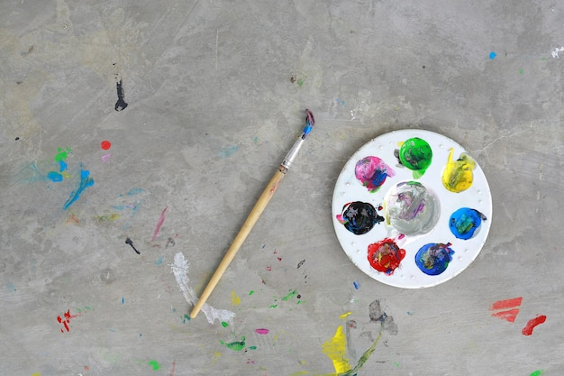 Top View Of Painted Brush Palette And Water Paint On Dirty Cement Floor Premium