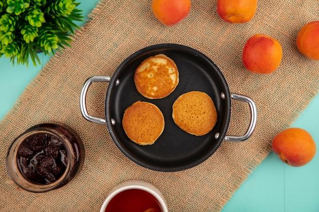 Вид сверху блинов на сковороде и абрикосов с клубничным вареньем на вретище на синем фоне Бесплатные Фотографии