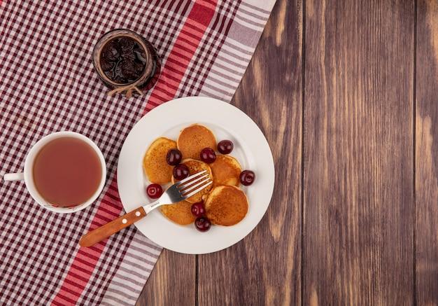 Вид сверху на блины с вишней и вилкой в тарелке и чашку чая с клубничным вареньем на клетчатой ткани на деревянном фоне с копией пространства Бесплатные Фотографии