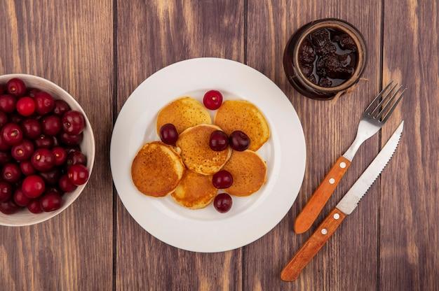 Вид сверху блинов с вишней в тарелке и миске вишни с клубничным вареньем и вилочным ножом на деревянном фоне Бесплатные Фотографии