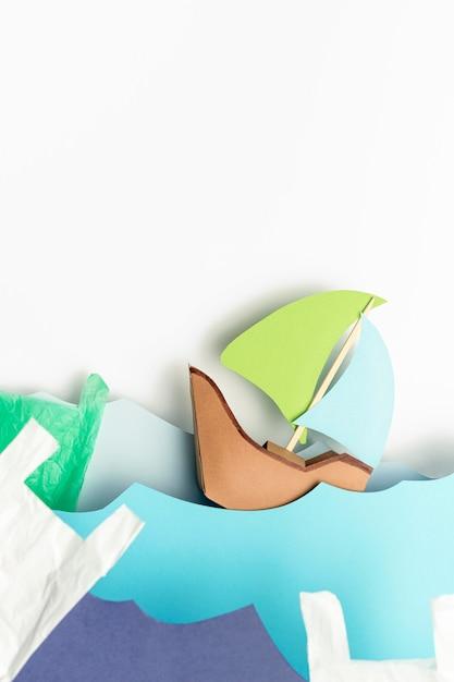 ビニール袋で波に紙の船のトップビュー 無料写真