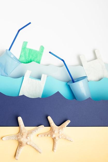 プラスチック製のカップとヒトデと紙の海の波のトップビュー 無料写真