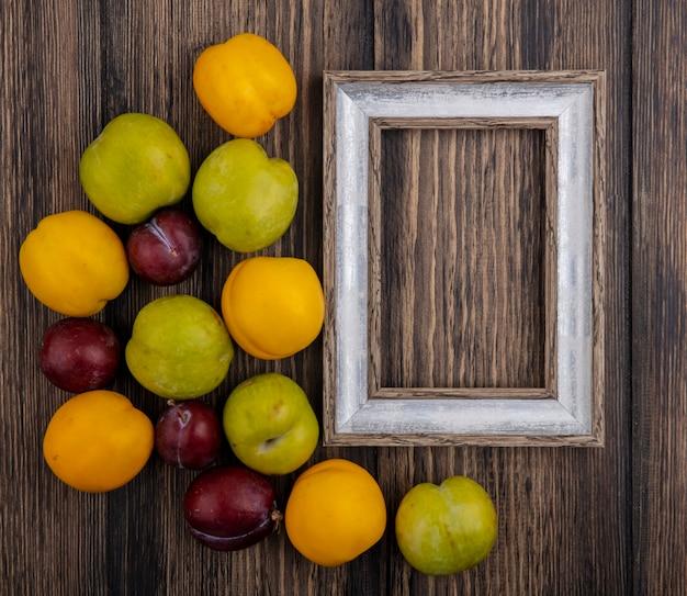 복사 공간 나무 배경에 프레임 Pluots 및 Nectacots로 과일의 패턴의 상위 뷰 무료 사진