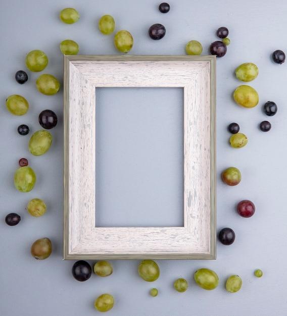 복사 공간 회색 배경에 프레임 주위에 포도 열매의 패턴의 상위 뷰 무료 사진