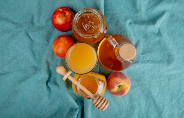 Вид сверху персикового сока в стеклянных и стеклянных банках с медом и персиковым джемом и свежими сладкими нектаринами на синем Бесплатные Фотографии