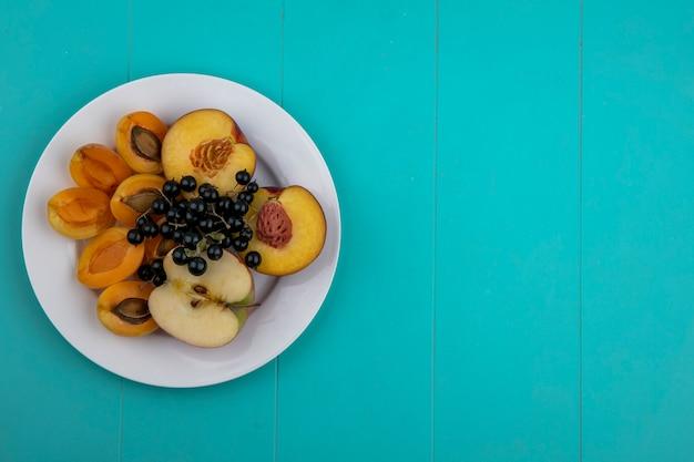 アプリコットと桃と水色の表面のプレートに黒スグリとリンゴのトップビュー 無料写真