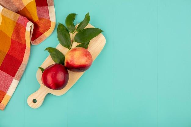 桃と葉のコピースペースと青の背景に格子縞の布でまな板の上から見る 無料写真