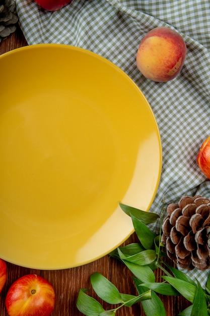Вид сверху персики и шишка вокруг пустой тарелке на ткани на деревянной поверхности, украшенной листьями Бесплатные Фотографии