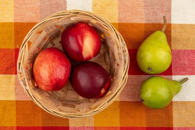 バスケットと梨の格子縞の布の背景に桃のトップビュー 無料写真