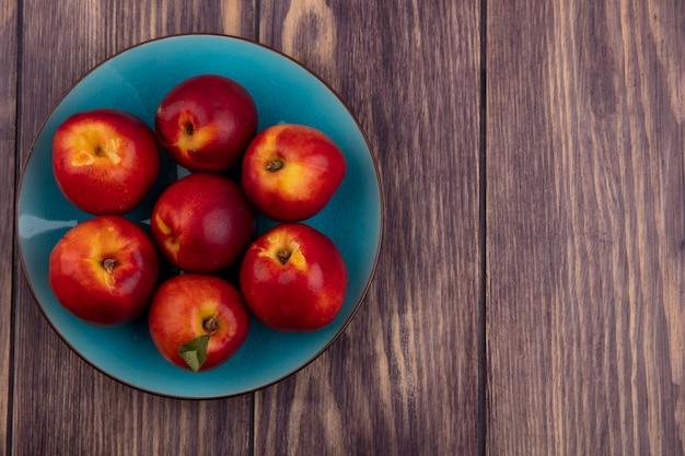 木の表面に青い皿に桃のトップビュー 無料写真