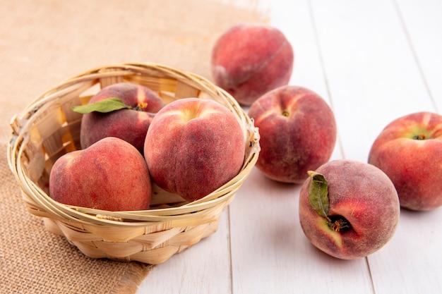 白い表面に分離された桃と袋布のバケツに桃のトップビュー 無料写真