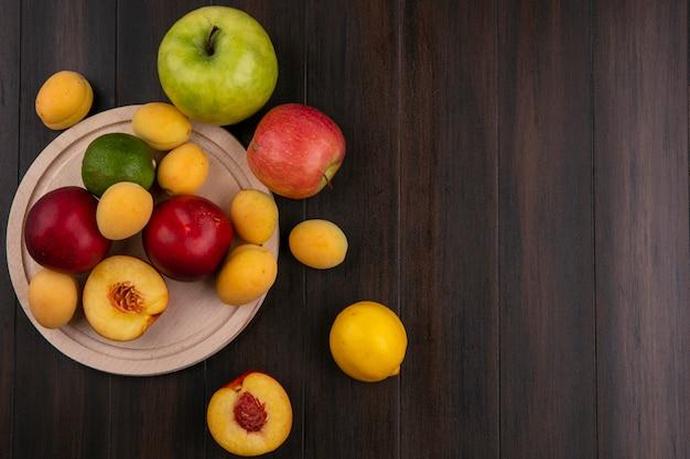 Вид сверху персиков на подставке с абрикосами и яблоками на деревянной поверхности Бесплатные Фотографии