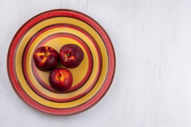 白い表面に黄赤プレート上の桃のトップビュー 無料写真