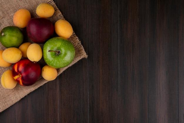Вид сверху персиков с абрикосами и зеленым яблоком на бежевой салфетке на деревянной поверхности Бесплатные Фотографии