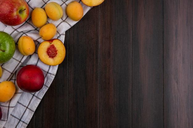Вид сверху персиков с абрикосами и яблоками на полотенце на деревянной поверхности Бесплатные Фотографии