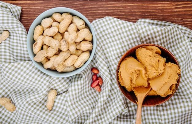 Вид сверху арахисового масла в деревянной миске с миской, наполненной арахисом на деревянном фоне Бесплатные Фотографии
