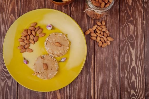 Вид сверху арахисового масла с миндалем на хрустящих рисовых крекерах на желтой керамической пластине с рассеянным миндалем на деревянном фоне Бесплатные Фотографии