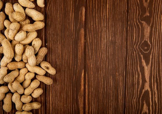 Вид сверху арахиса в скорлупе, разбросанных на деревянном фоне с копией пространства Бесплатные Фотографии