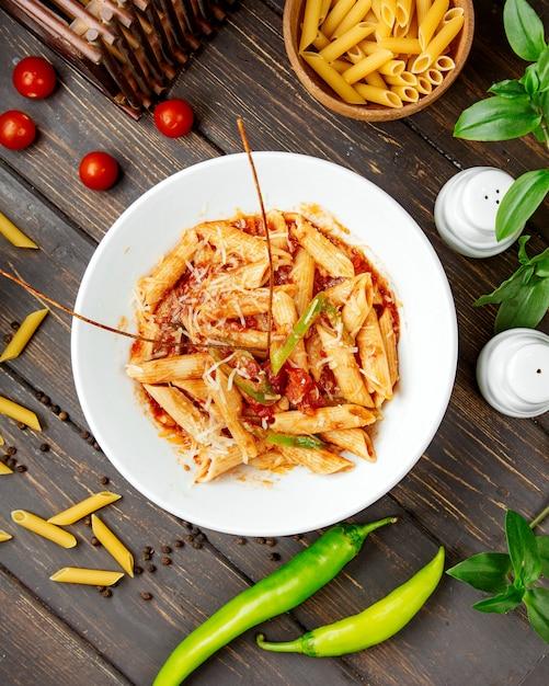 Вид сверху пасты пенне с томатным соусом и болгарским перцем Бесплатные Фотографии