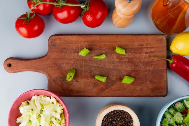 Вид сверху ломтики перца на разделочной доске с ломтиками капусты помидоры овощной салат семена черного перца масло лимона на синем фоне Бесплатные Фотографии