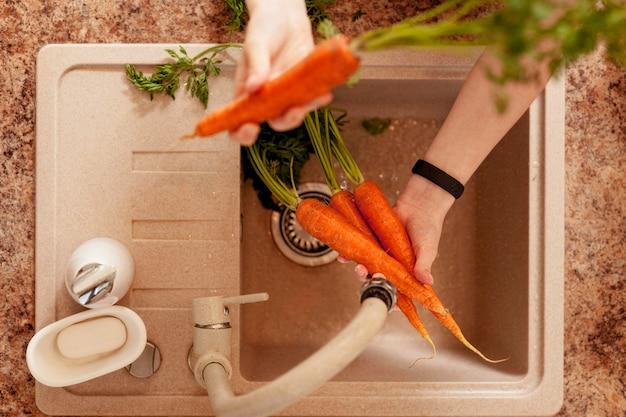 夕食の準備でニンジンを洗う人のトップビュー 無料写真