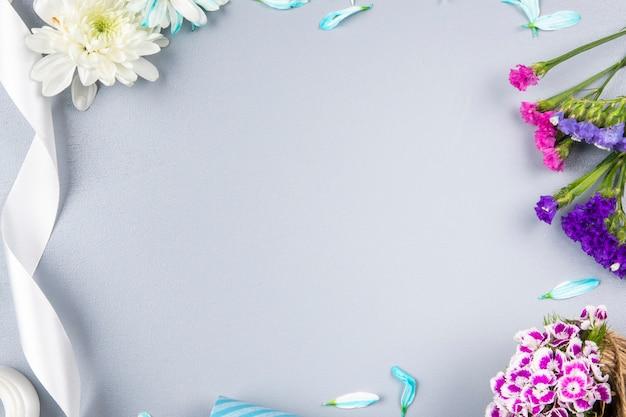 Вид сверху розовые и фиолетовые цветы статицы с белой хризантемы и ленты на белом столе с копией пространства Бесплатные Фотографии