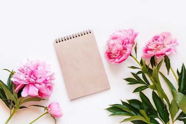 コピースペース付きのノートブックとピンクの牡丹の花の平面図です。 Premium写真