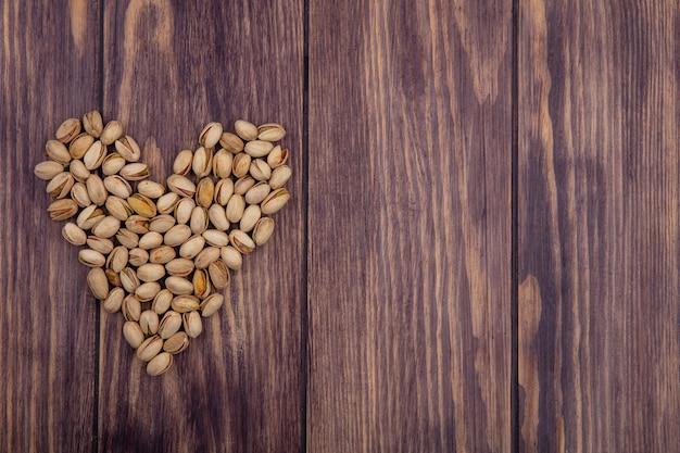 Вид сверху сердца фисташек на деревянной поверхности Бесплатные Фотографии