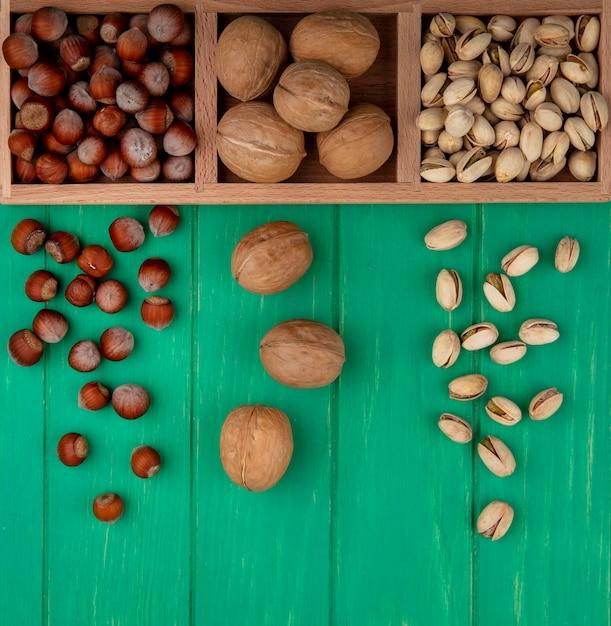 Вид сверху фисташек с фундуком и грецкими орехами на деревянной подставке на зеленой поверхности Бесплатные Фотографии