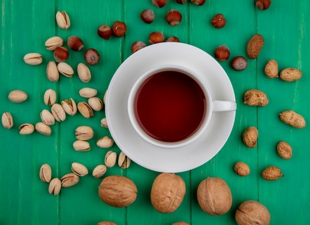 Вид сверху фисташек с фундуком, грецкими орехами и арахисом в мисках разной формы и чашке чая на зеленой поверхности Бесплатные Фотографии