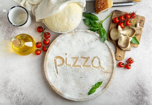 Вид сверху на тесто для пиццы с грибами и помидорами и слово, написанное в муке Бесплатные Фотографии
