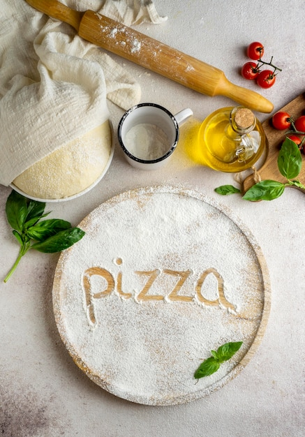 Вид сверху на тесто для пиццы с помидорами и словом, написанным в муке Бесплатные Фотографии
