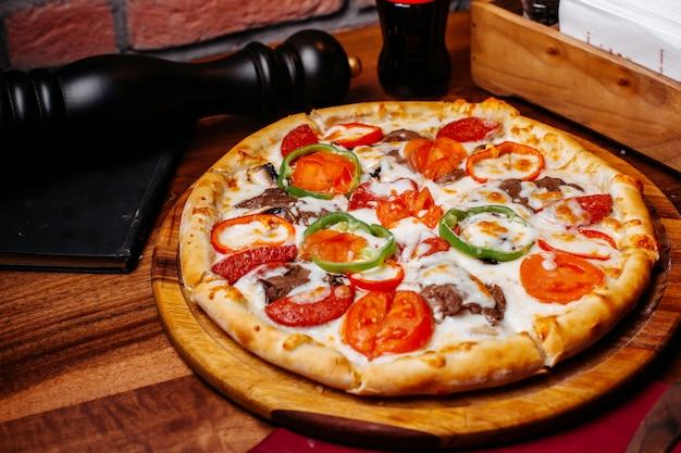 木の板にトマトのカラフルなピーマンサラミとオリーブで満たされたピザのトップビュー 無料写真