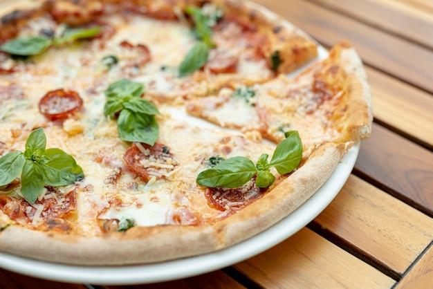 Вид сверху пиццы с базиликом на деревянный стол Бесплатные Фотографии