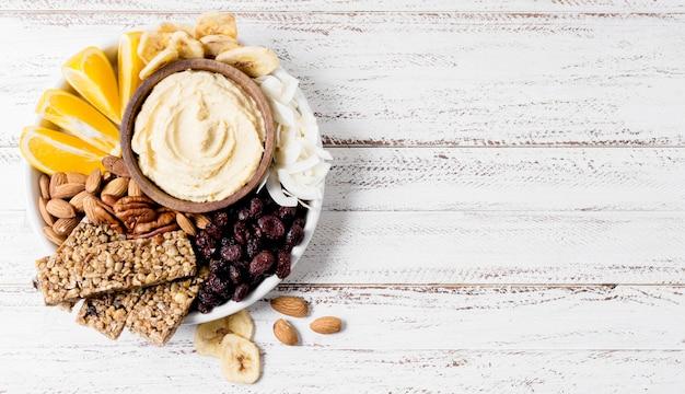 Вид сверху пластины с ассортиментом орехов и зерновых батончиков с копией пространства Бесплатные Фотографии